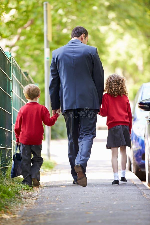 Pai Walking To School com as crianças na maneira de trabalhar imagens de stock