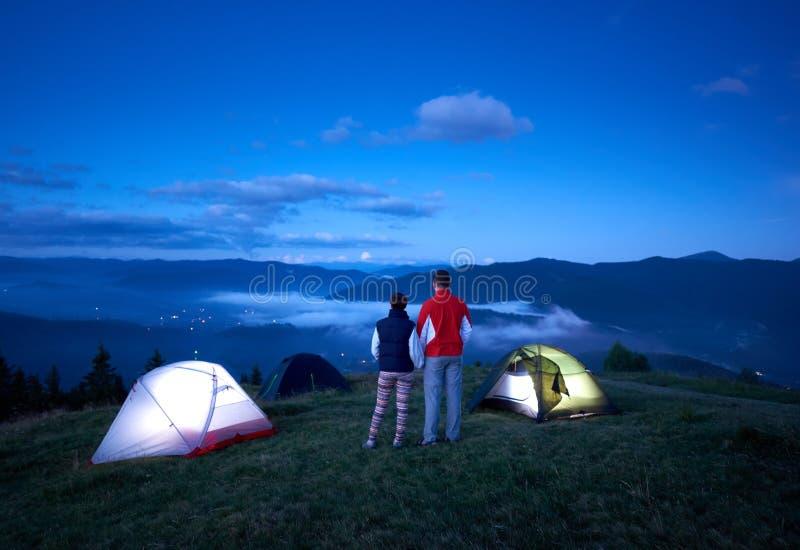 Paia attive di retrovisione che si tengono per mano godere dell'alba vicino che si accampa in montagne immagine stock libera da diritti