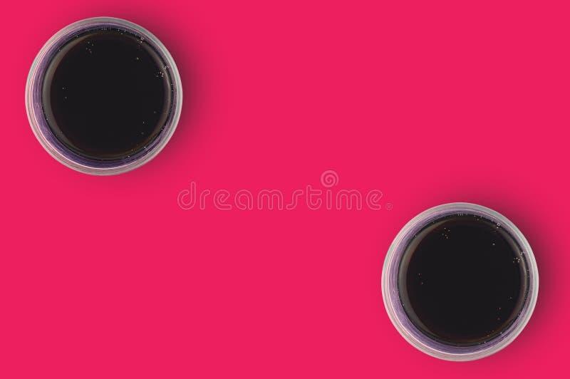 Paia dei vetri pieni di cola aerata con le bolle sulla tavola rossa in cucina copi lo spazio per il vostro testo Vista superiore fotografia stock