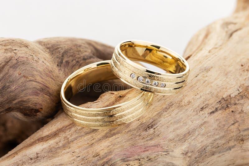 Paia delle bande di superficie strutturate della fede nuziale dell'oro su fondo di legno immagini stock