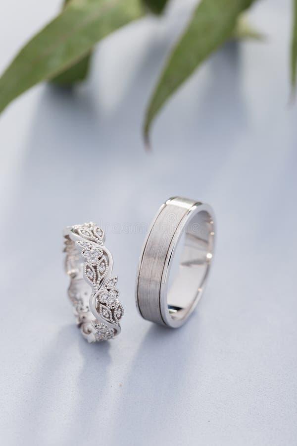 Paia delle fedi nuziali d'argento con i diamanti su fondo blu immagine stock