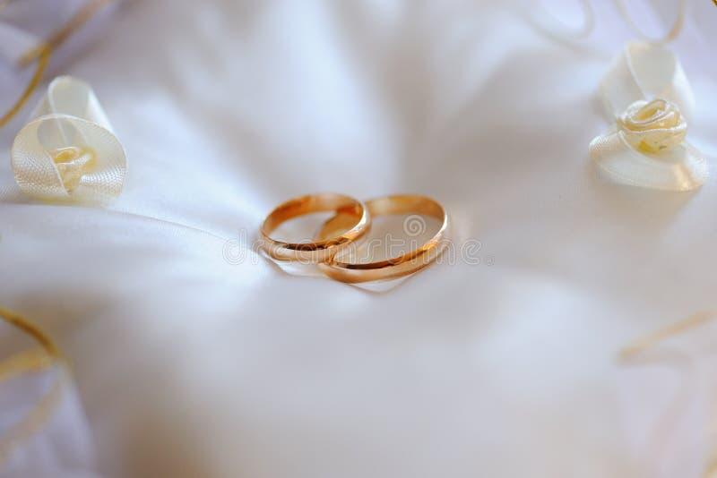 Paia delle fedi nuziali dell'oro su un cuscino bianco fotografia stock