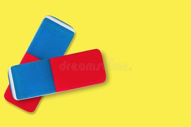 Paia delle gomme di gomma rettangolari per la matita e l'inchiostro della penna su fondo giallo immagini stock
