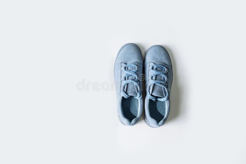 Paia delle scarpe blu della pelle scamosciata con i pizzi spessi su un fondo bianco fotografia stock