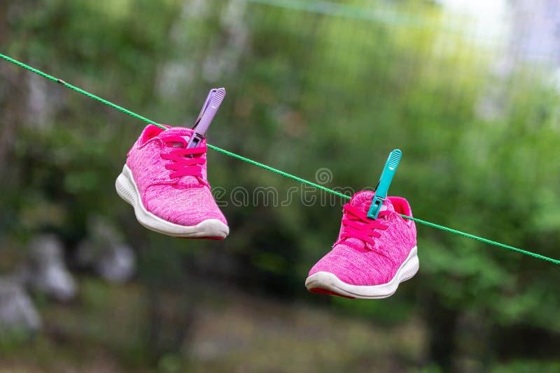 Paia delle scarpe da tennis luminose di forma fisica di sport appese sulla molletta da bucato al cortile dopo la lavanderia all'a fotografie stock libere da diritti