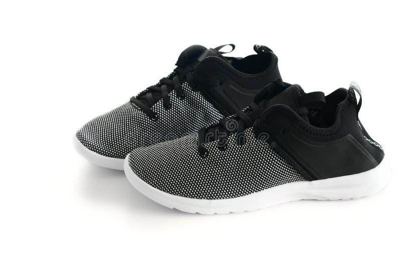 Paia delle scarpe da tennis nere delle donne isolate su fondo bianco Molestia immagini stock