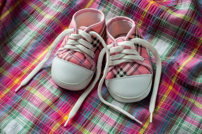 Paia delle scarpe da tennis su tessuto variopinto fotografia stock