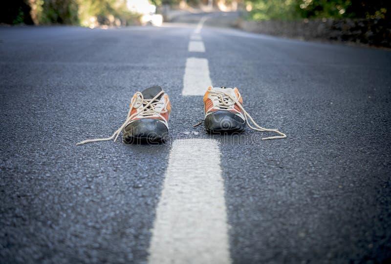 Paia delle scarpe da tennis sulla strada immagini stock