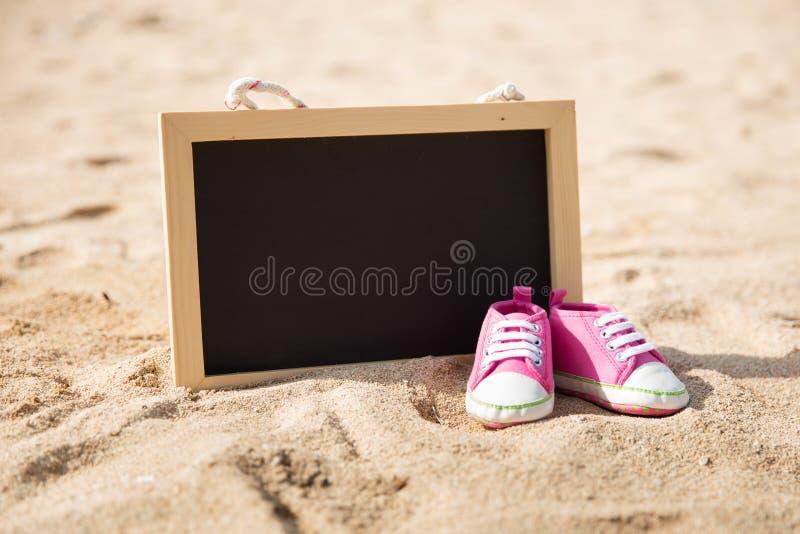 Paia delle scarpe del bambino e di mini bordo di gesso sulla sabbia immagine stock libera da diritti