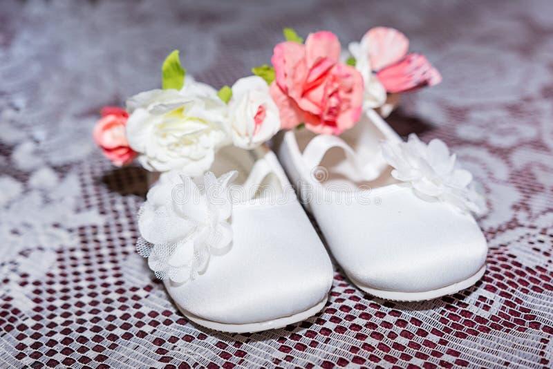 Paia delle scarpe di bambino bianche sui pantaloni e sulla camicia a cerimonia di battesimo di battesimo alla cappella della chie fotografie stock