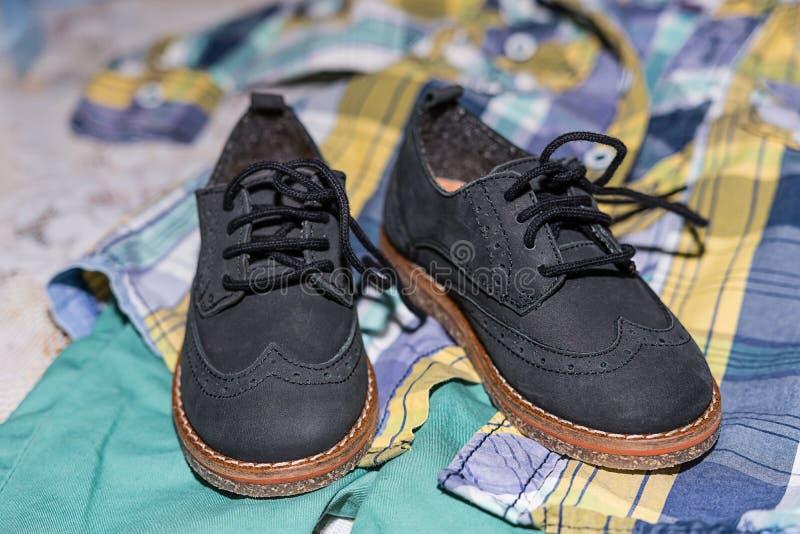 Paia delle scarpe di bambino blu scuro sui pantaloni e sulla camicia a cerimonia di battesimo di battesimo alla cappella della ch fotografia stock