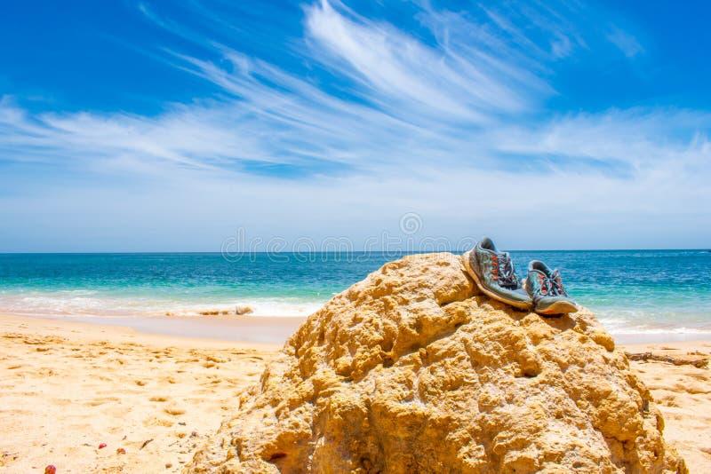 Paia delle scarpe di sport che si trovano sulla pietra sulla spiaggia contro il cielo blu Praia de Marinha in Algarve, Portogallo immagini stock