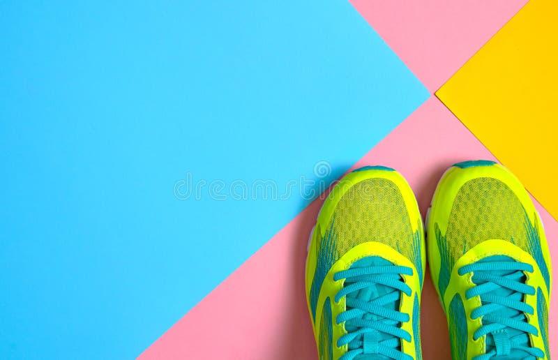 Paia delle scarpe di sport su fondo variopinto Nuove scarpe da tennis sul fondo pastello blu e giallo di rosa, spazio della copia fotografia stock libera da diritti