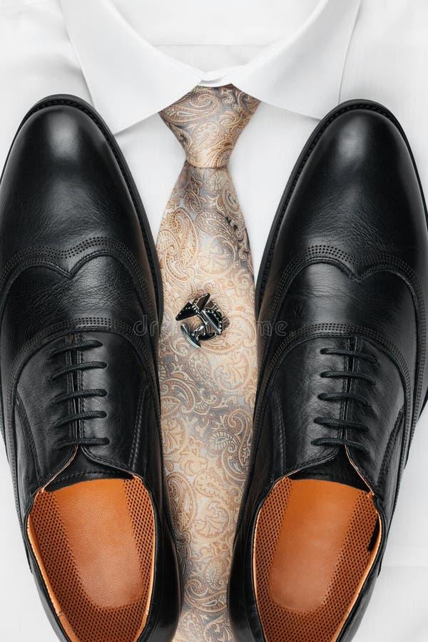 Paia delle scarpe nere classiche che stanno su una camicia e su un legame Modo del ` s degli uomini immagine stock libera da diritti