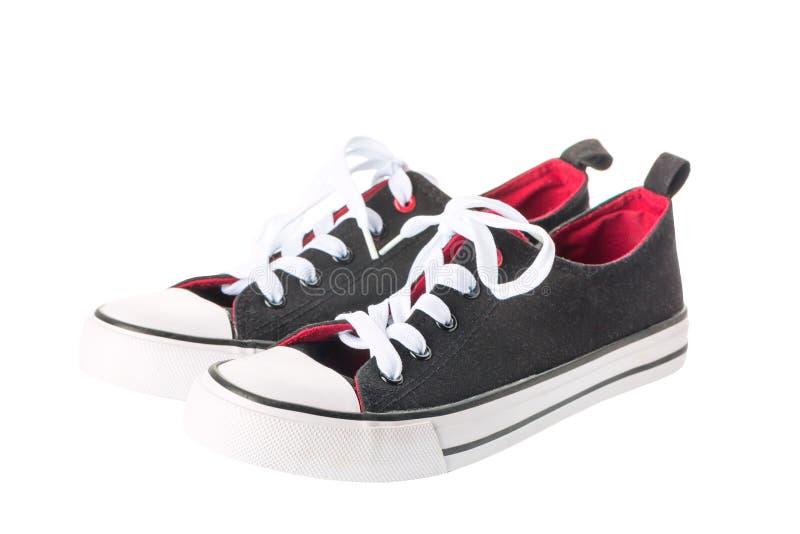 Paia di nuovi gumshoes delle scarpe da tennis su fondo bianco fotografia stock