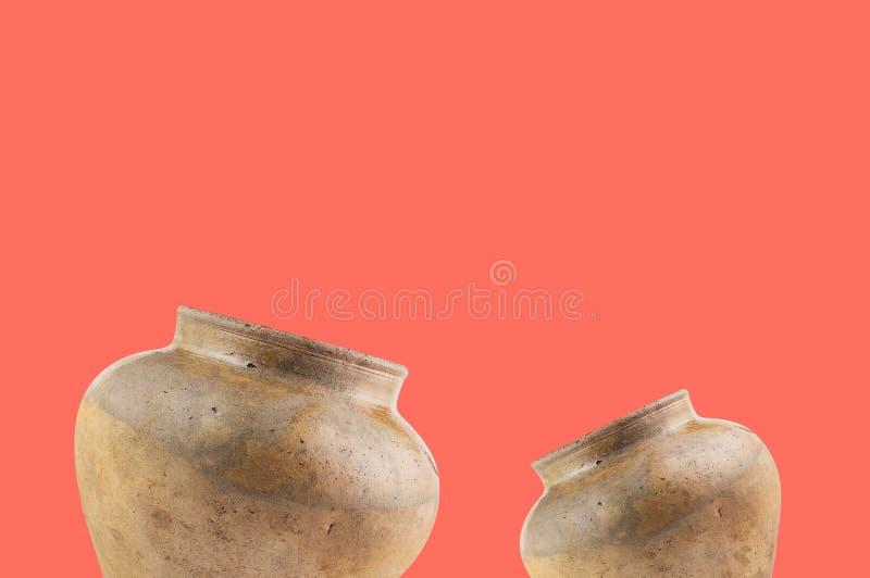 Paia di vecchi vasi consumati e sporchi antichi sulla tavola di colore di corallo con lo spazio della copia per il vostro testo fotografie stock