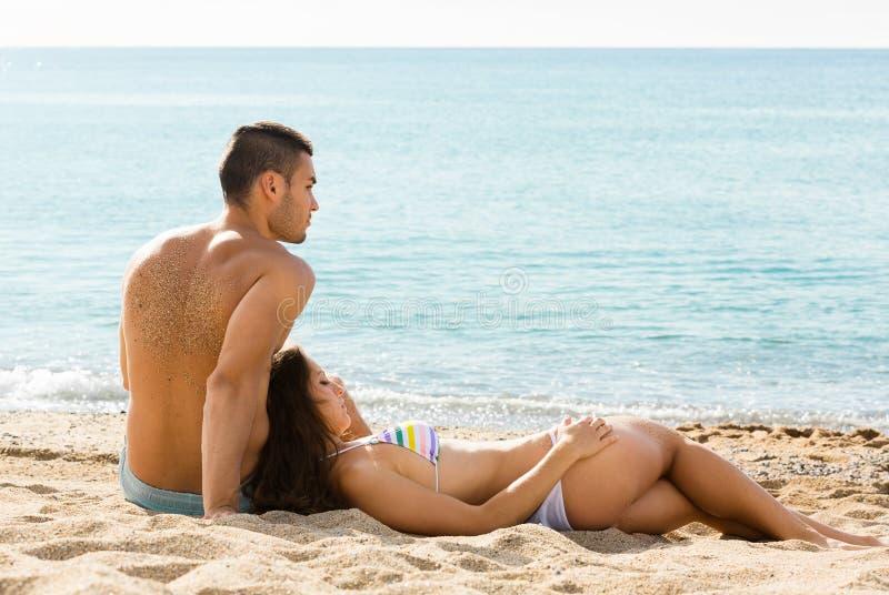 Paia felici che si rilassano sulla spiaggia di sabbia fotografie stock libere da diritti