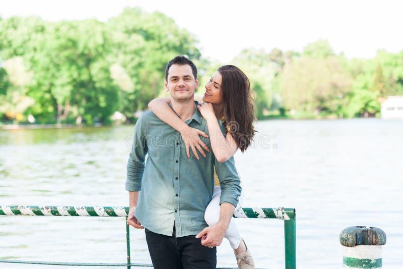 Paia felici di maschio e della femmina che abbracciano e che si divertono nel parco della città immagini stock libere da diritti