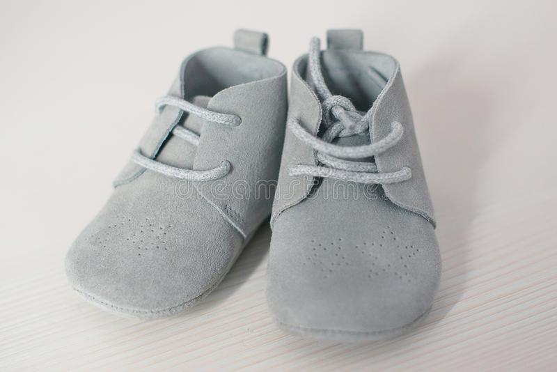 Paia isolate delle scarpe di bambino blu della pelle scamosciato, calzature molli con stringhe dei bambini svegli sole immagine stock