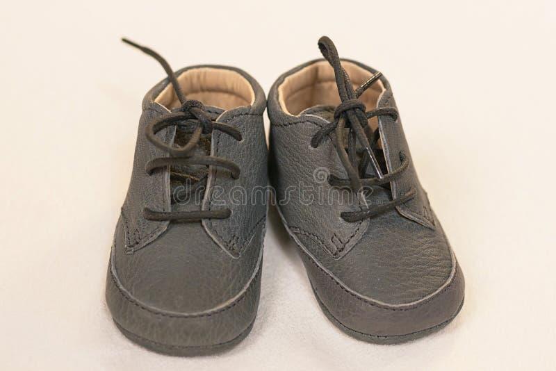 Paia isolate delle scarpe di cuoio grige del neonato, calzature molli con stringhe dei bambini svegli le sole fotografie stock libere da diritti