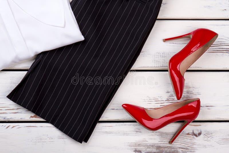 Paia piane di disposizione delle scarpe e dei pantaloni brillanti rossi del tallone fotografia stock