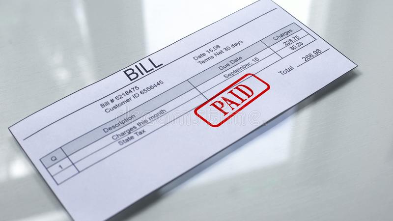 Paid seal stamped on bill, payment for services, month charges, close up. Stock photo royalty free stock photo