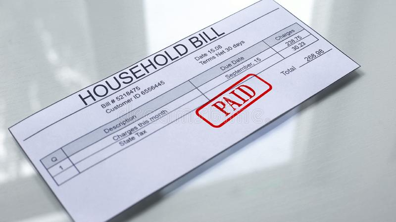 Paid seal stamped on household bill, services payment, month expenses tariff. Stock photo royalty free illustration
