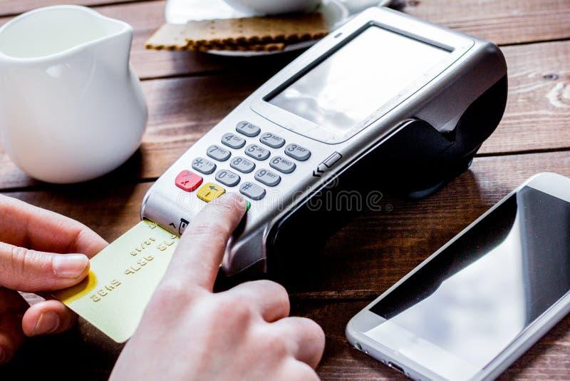 Paiement dans le concept de café avec la carte et le terminal sur le backgro en bois photo libre de droits
