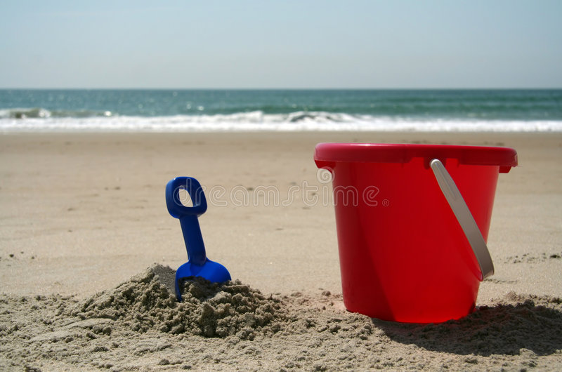 Pail and shovel at the beach. Red pail and blue shovel in the sand at the beach royalty free stock photo