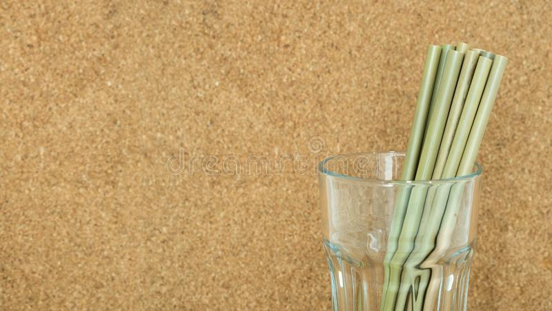 Paille en bambou d'Eco en verre clair avec le fond de liège photographie stock libre de droits