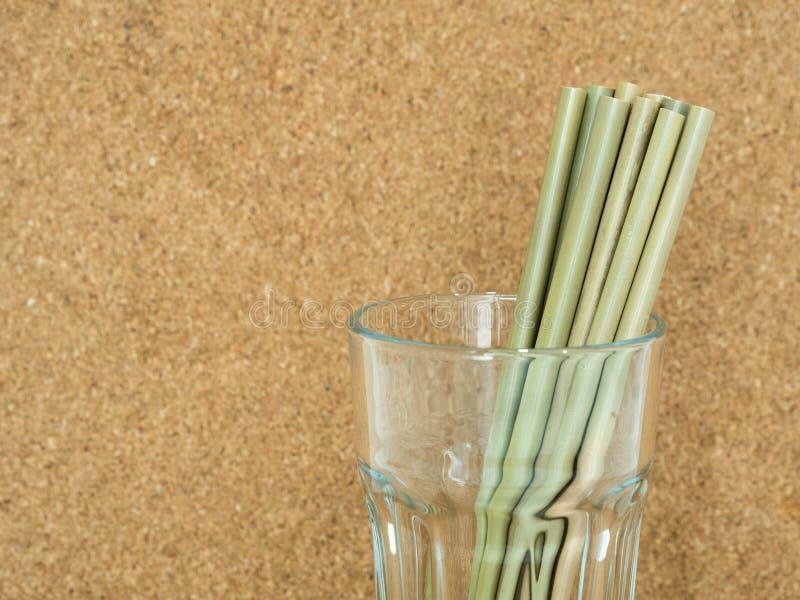 Paille en bambou d'Eco en verre clair avec le fond de liège photographie stock