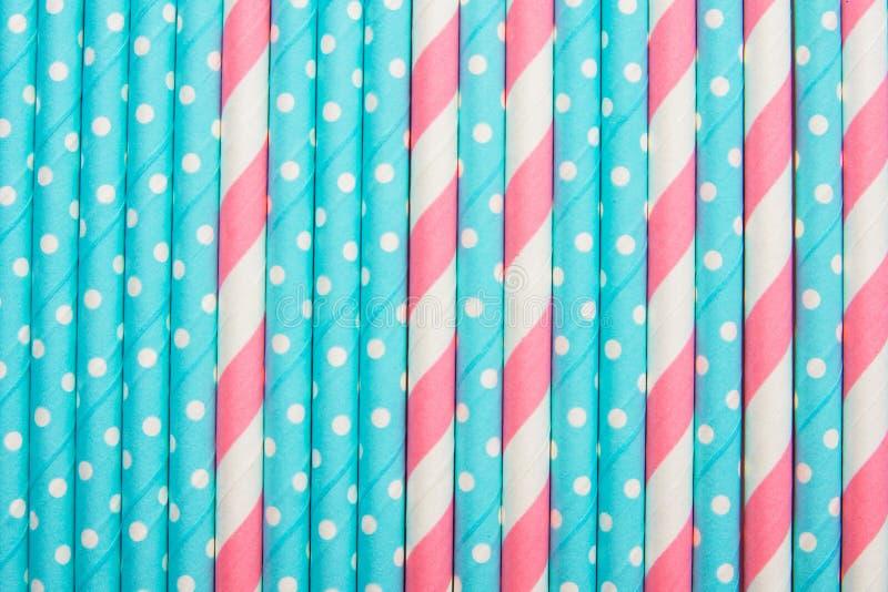 Pailles à boire rayées de polka de point de papier bleu de rose et blanc présentées aussi partout dans le contexte de modèle Célé photos libres de droits