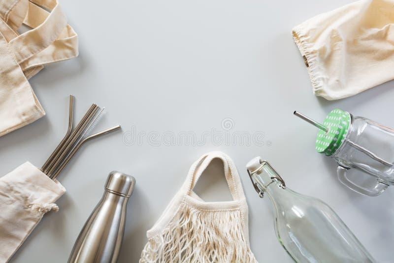 Pailles d'Eco, sac de coton, verre et bouteille métalliques naturels en métal sur le gris Concept viable de mode de vie Les déche image libre de droits