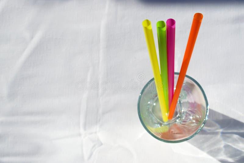 Pailles dans le verre sur le fond blanc photographie stock libre de droits