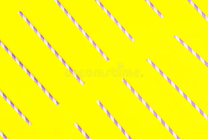 Pailles de papier pourpres sur le fond jaune de couleur images stock