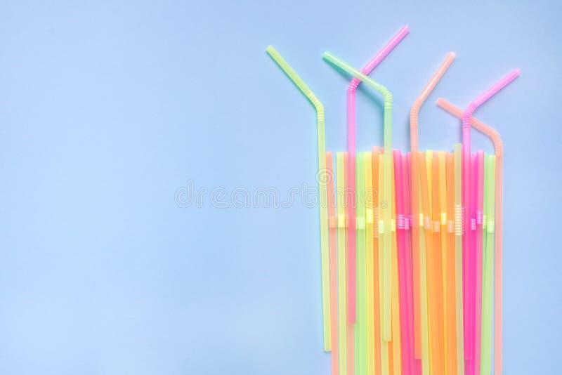 Pailles en plastique color?es sur le fond bleu Tubes de cocktail images stock