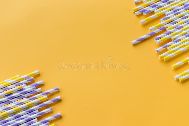 Pailles rayées de boissons de différentes couleurs dans la rangée d'isolement sur le fond jaune Concept de minimalisme style d'ar photographie stock