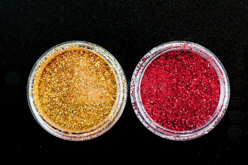 Paillettes d'or et rouges pour la manucure dans un pot sur un fond noir photographie stock