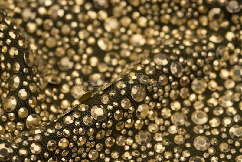 Paillettes d'or sur le foyer sélectif de textile de texture photographie stock libre de droits