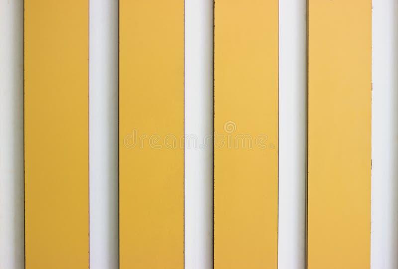 Painéis amarelos e brancos decorativos da listra na parede imagens de stock