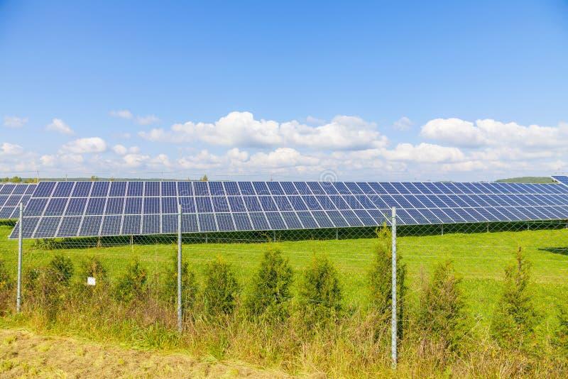 Painéis da energia solar no campo verde imagens de stock