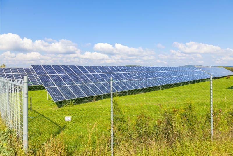 Painéis da energia solar no campo verde, céu azul fotos de stock