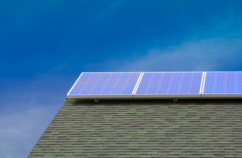 Painéis solares do picovolt no telhado com céu azul fotografia de stock royalty free