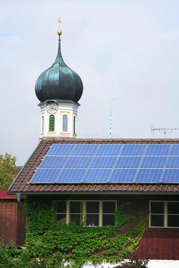 Painéis solares e steeple fotografia de stock