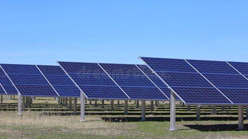 Painéis solares em um campo com céu azul fotos de stock royalty free