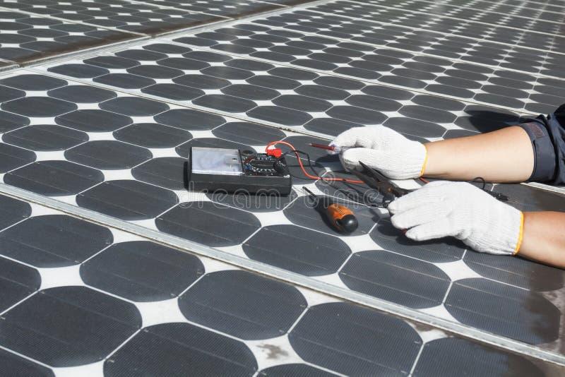 Painéis solares fotovoltaicos da energia do reparo do trabalhador imagens de stock