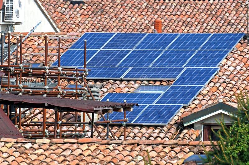 Painéis solares fotovoltaicos eficientes de poupança de energia verdes limpos renováveis no telhado suburbano da casa do frontão  fotos de stock royalty free