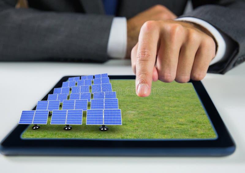 painéis solares na grama na tabuleta com mão do homem de negócios fotografia de stock