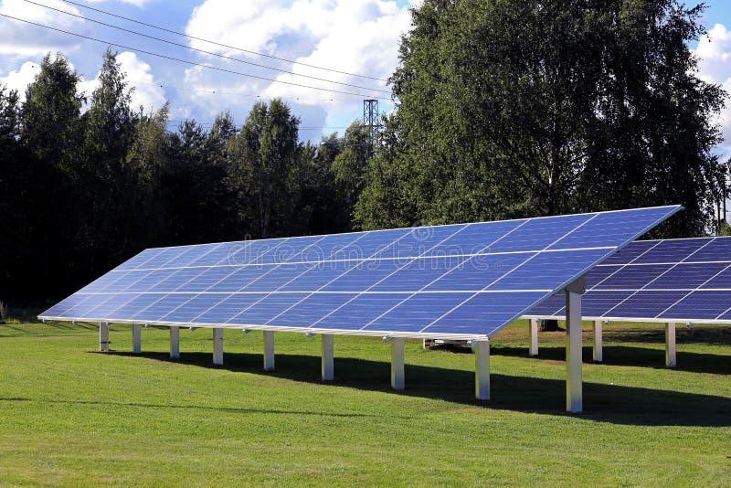 Painéis solares no campo de grama verde fotografia de stock royalty free