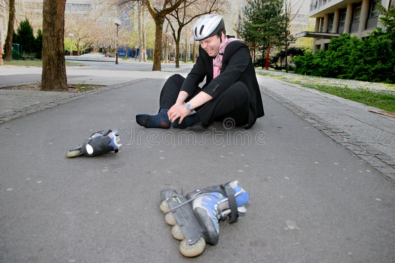 Pain. Businessman in a lot of pain from roller-blading royalty free stock photography